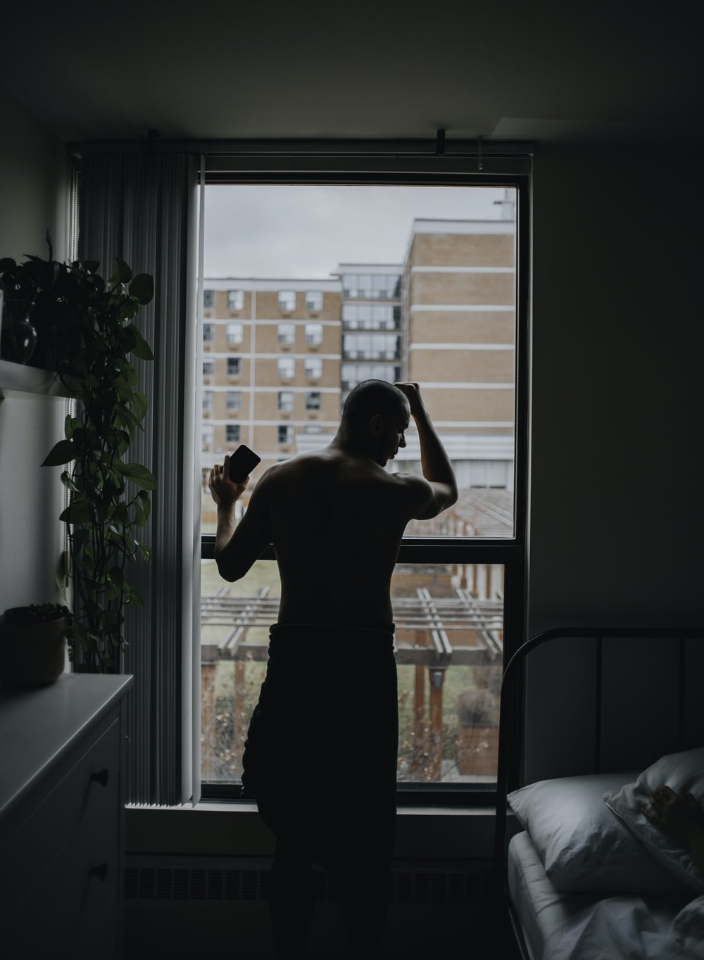 man standing by the window beside bed