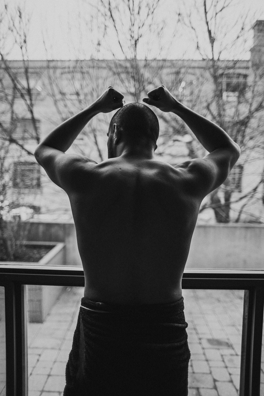 topless man standing near window