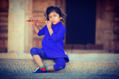 selective focus photography of girl playing flute flute teams background