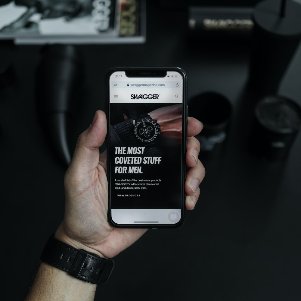 black smartphone displaying the most coveted stuff for men text