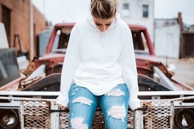 woman in jeans and sweater sitting on top of hood of vehicle at daytime kansas zoom background
