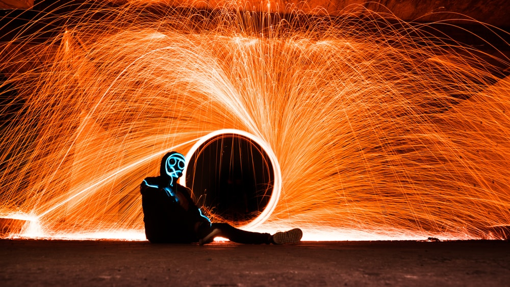 fire dancing person while sitting on floor