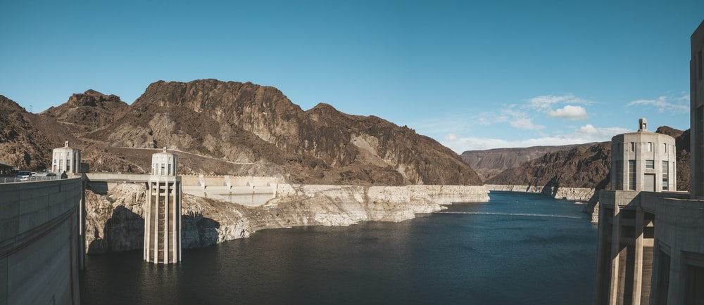 gray dam near mountains during day