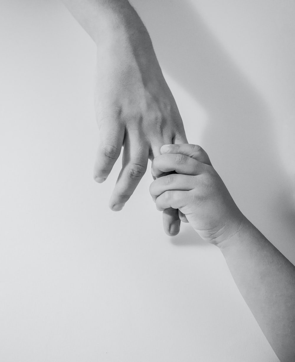 grayscale photo of to hands