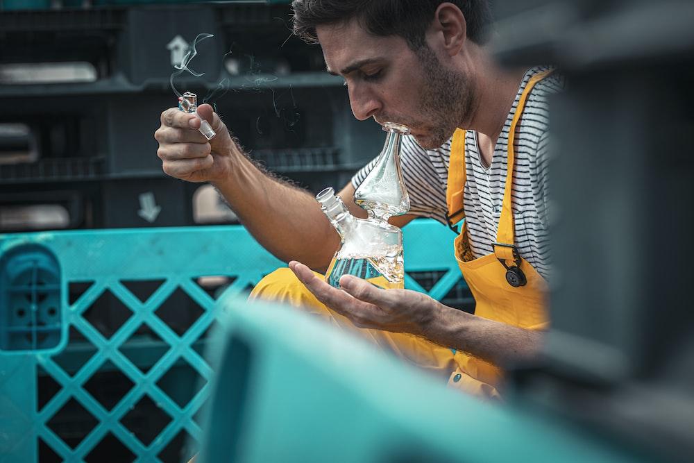 man using glass smoking device