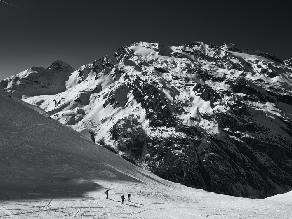 three person standing on mountain with snow