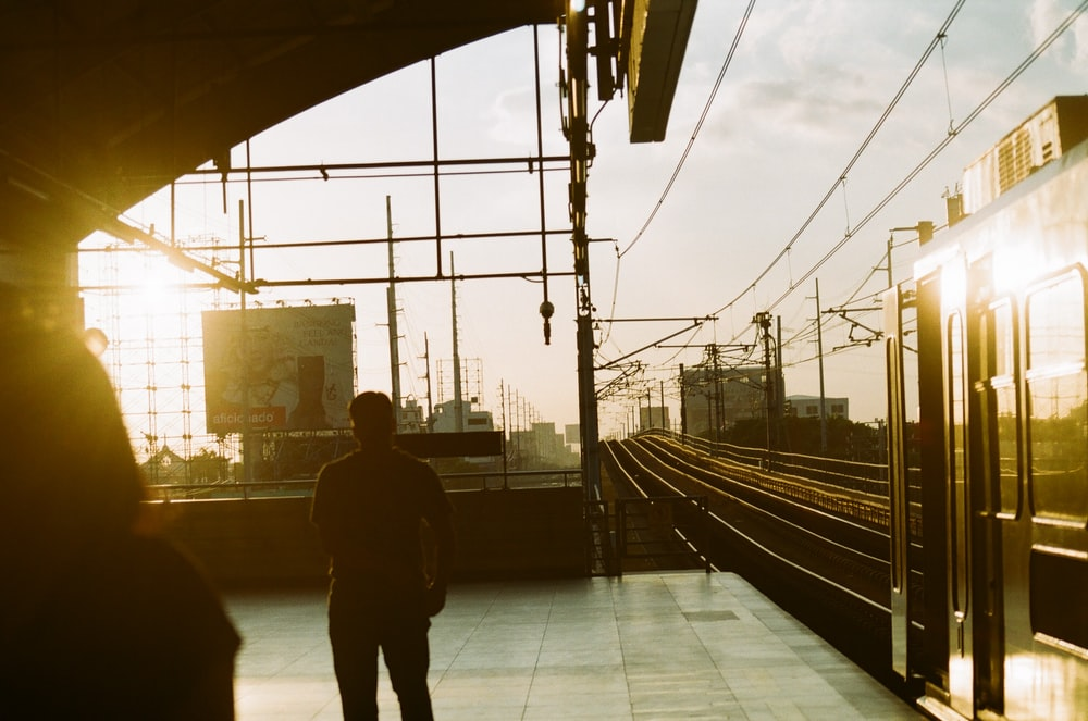 silhouette photography of man standing near railways