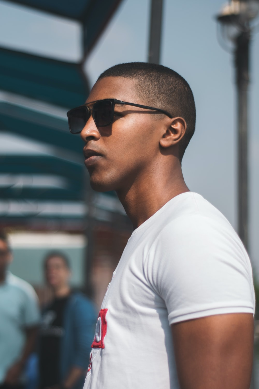 man wearing black sunglasses near people
