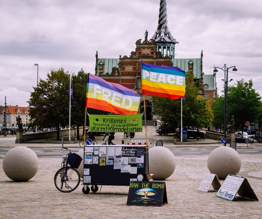 LGBT banner near bike on street viewing buildings during daytime