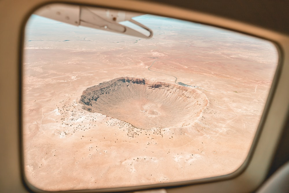 aircraft window view of brown crater