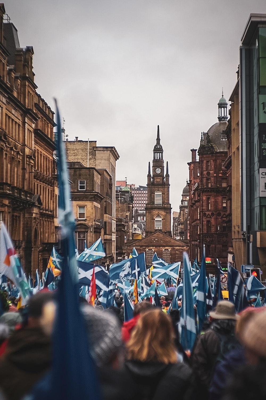 people on street holding scotland flag