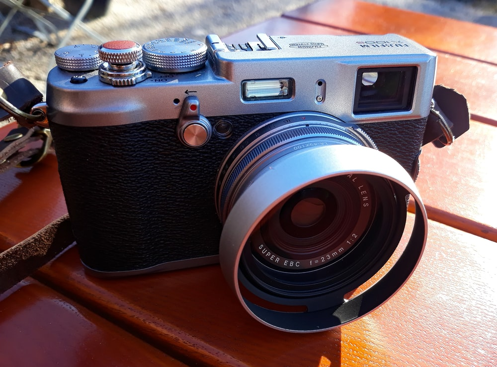 black and silver camera on wooden surface
