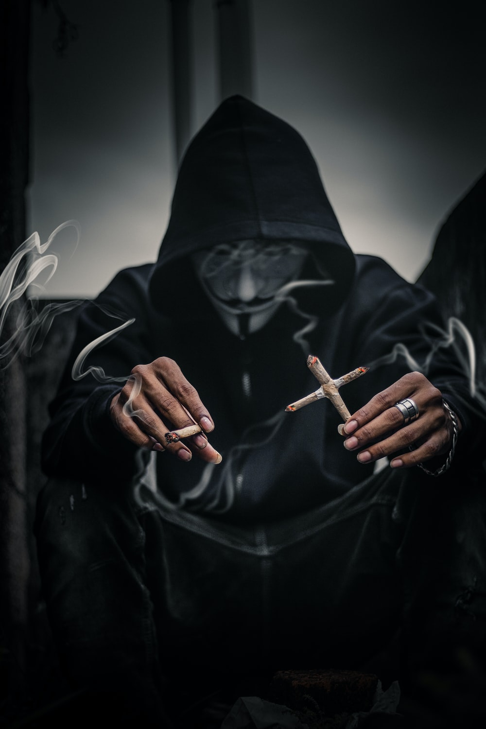 person in Guy Fawkes mask holding cross-shaped lighted cigarettes on his left with lighted joice on right hand