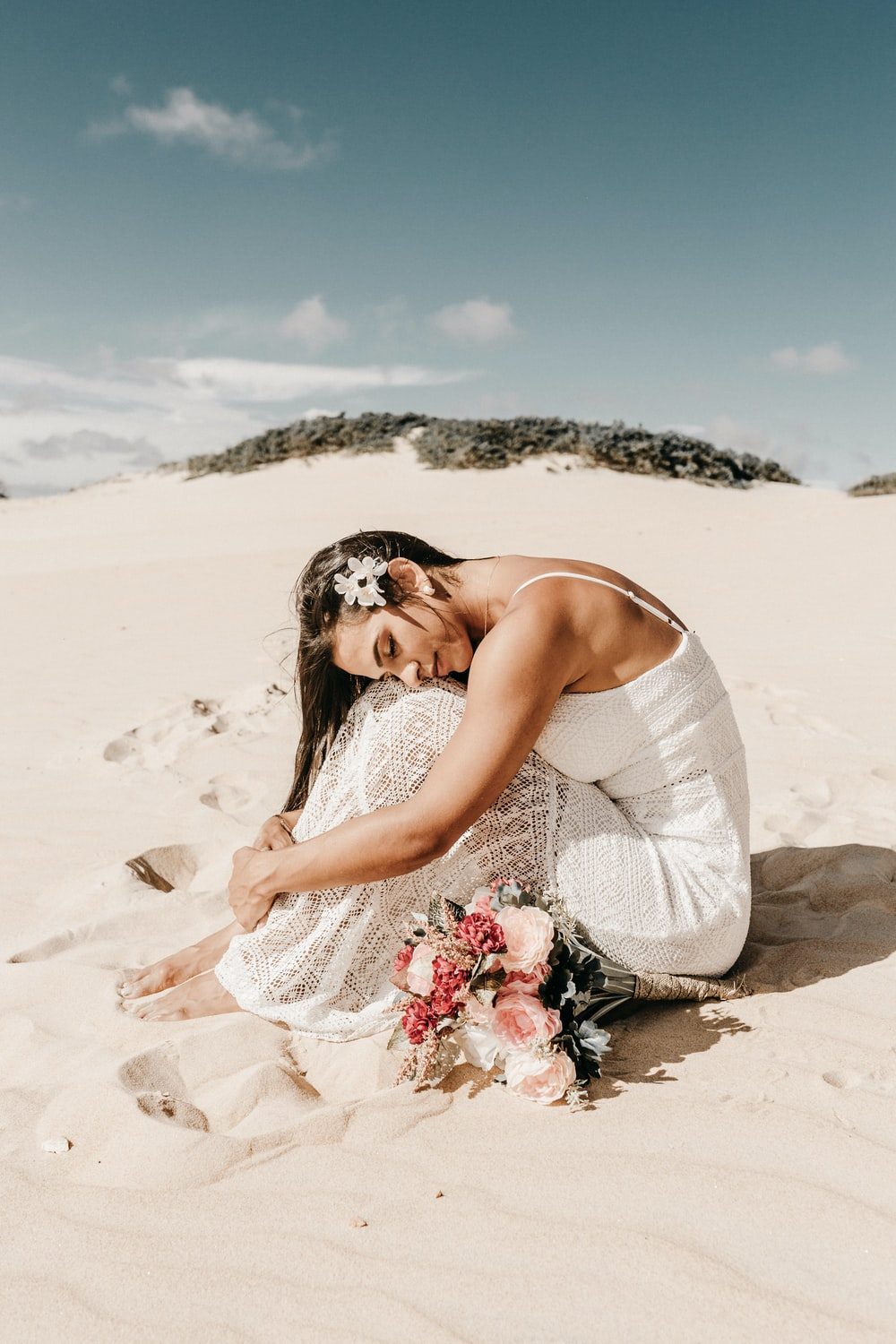 woman in white spaghetti strap dress sitting on sand