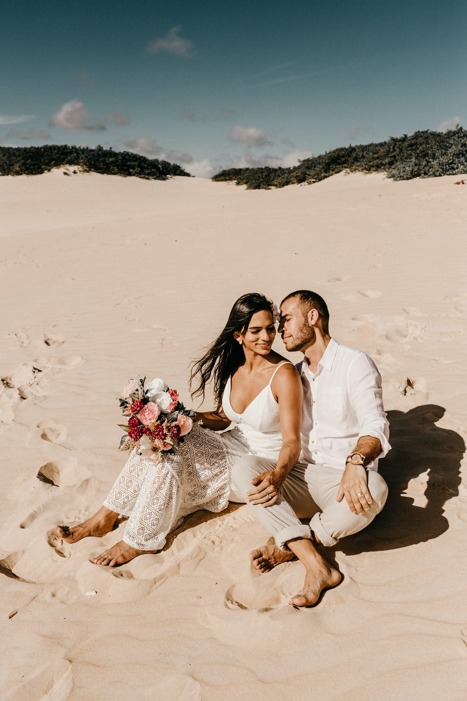 couple sitting on shore during daytime