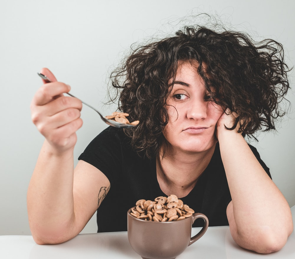 woman with messy hair wearing black crew-neck t-shirt holding spoon with cereals on top
