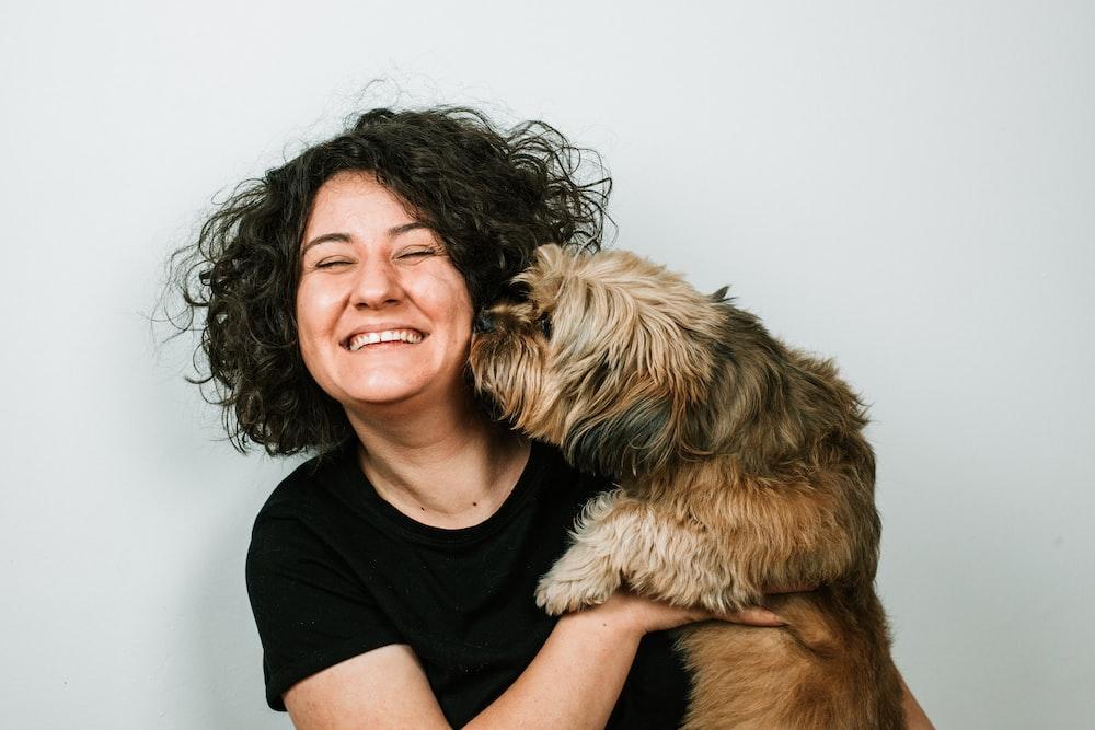 dog kissing woman in black crew-neck shirt