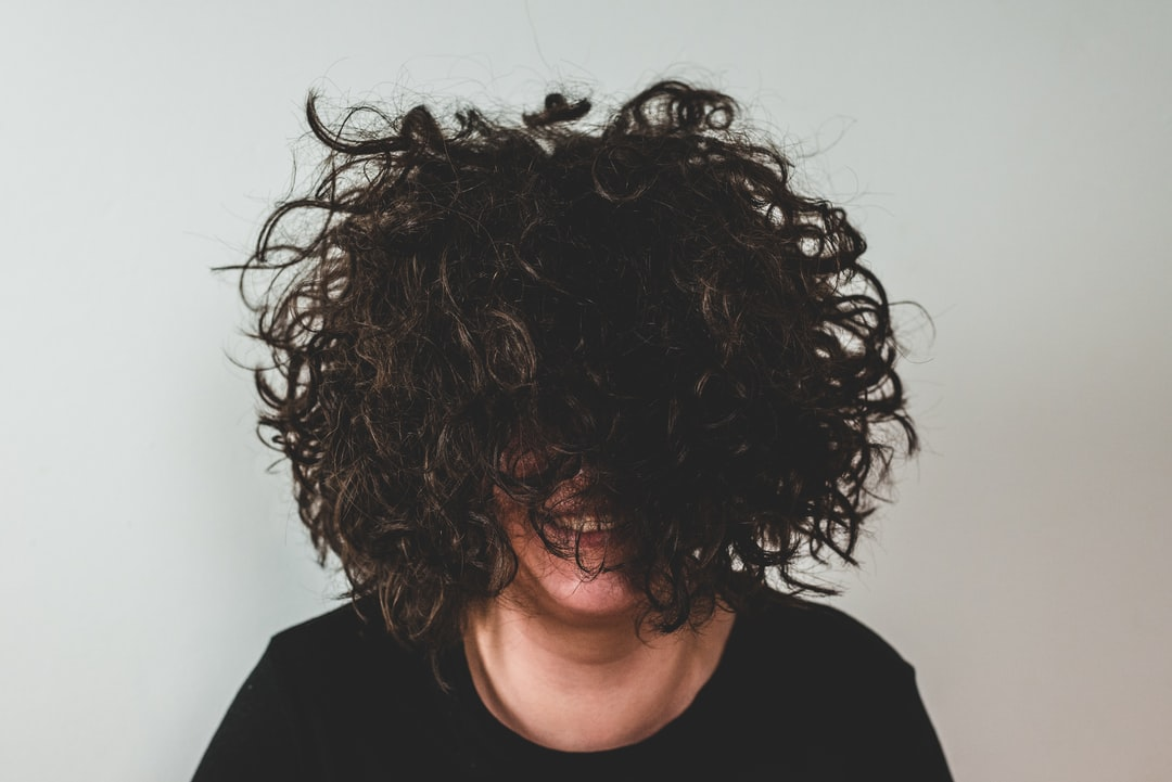 Girl With Curly Hair In Front of Her Face - unsplash