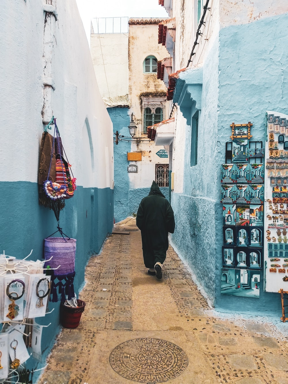 person wearing hooded jacket walking on alley between buildings during daytime