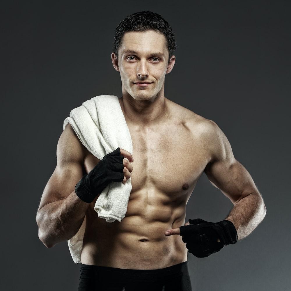 topless man wearing black gloves holding towel