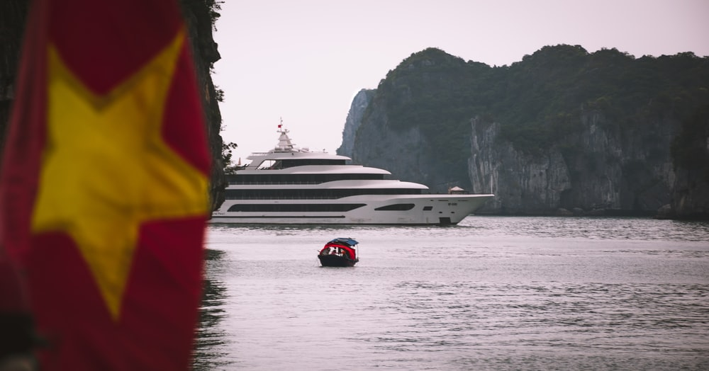 white yacht near islet during daytime