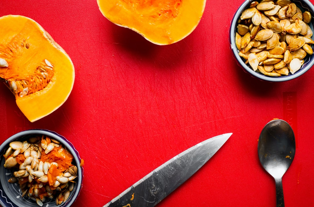 knife, squash slices and seeds