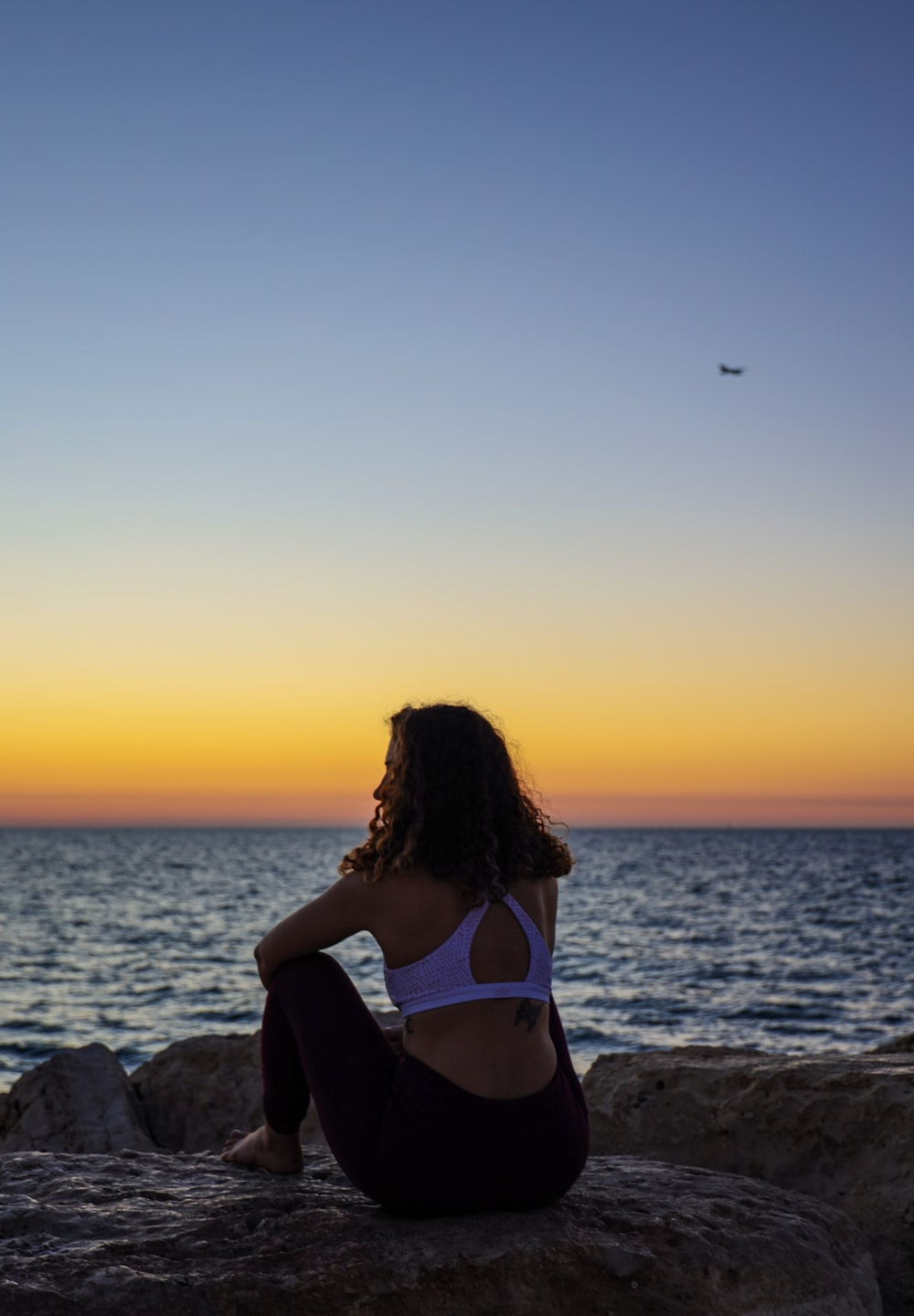 woman sitting on a rock facing the sea during golden hour