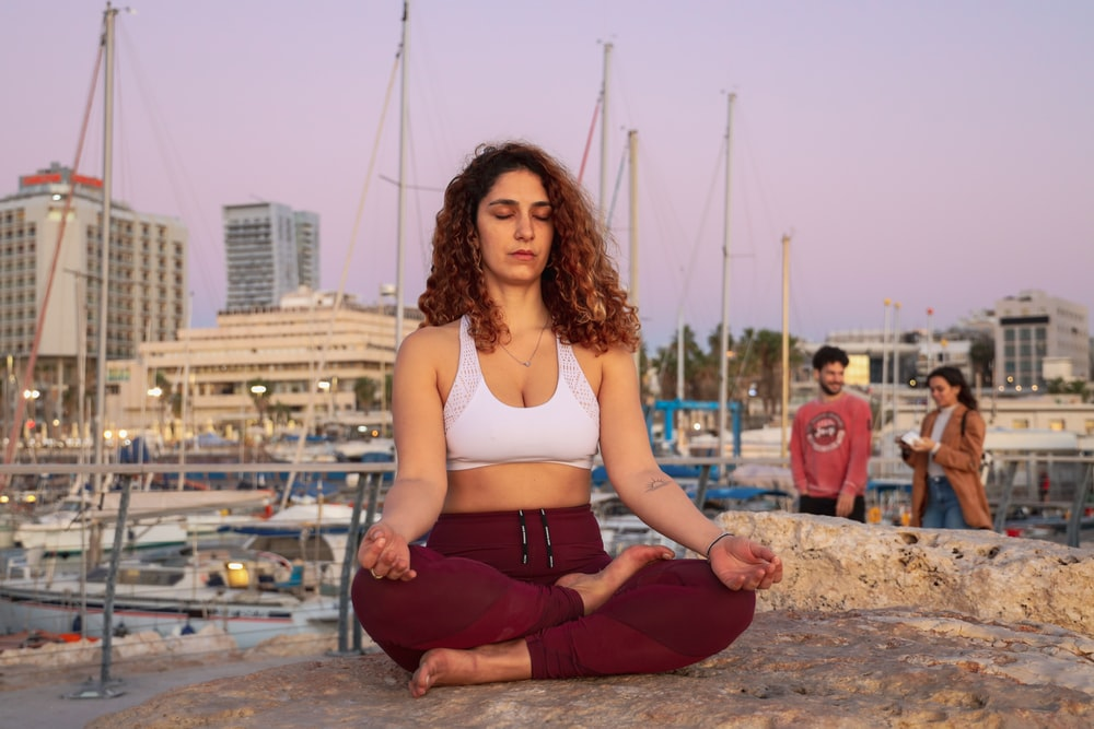 meditating woman in white sports bra and red yoga pants outfit