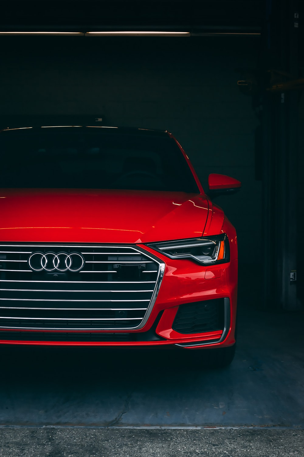red Audi vehicle parked inside garage with light