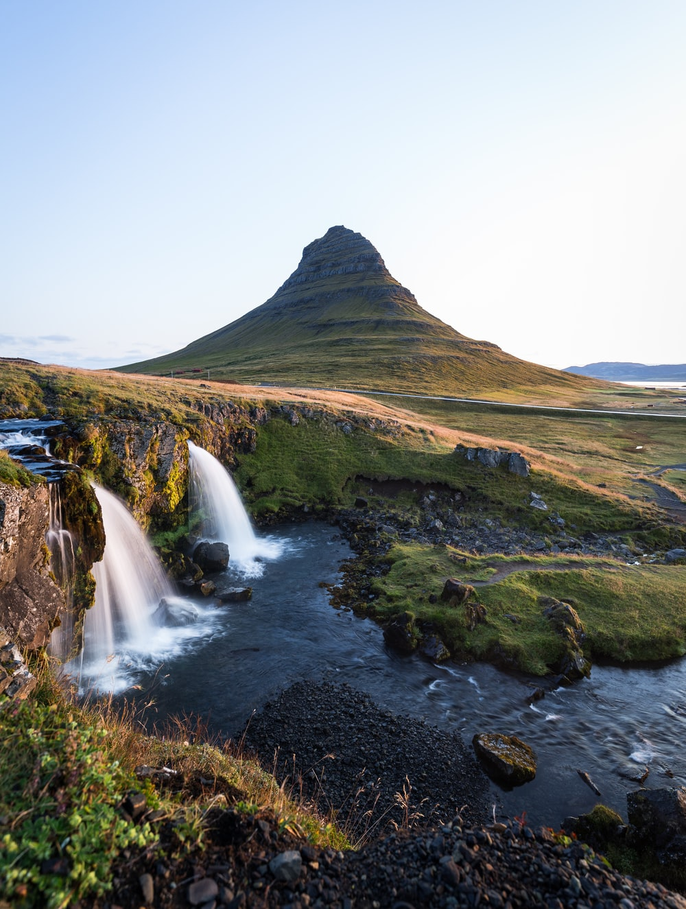 landscape photography of waterfalls viewing mountain and green field during daytime