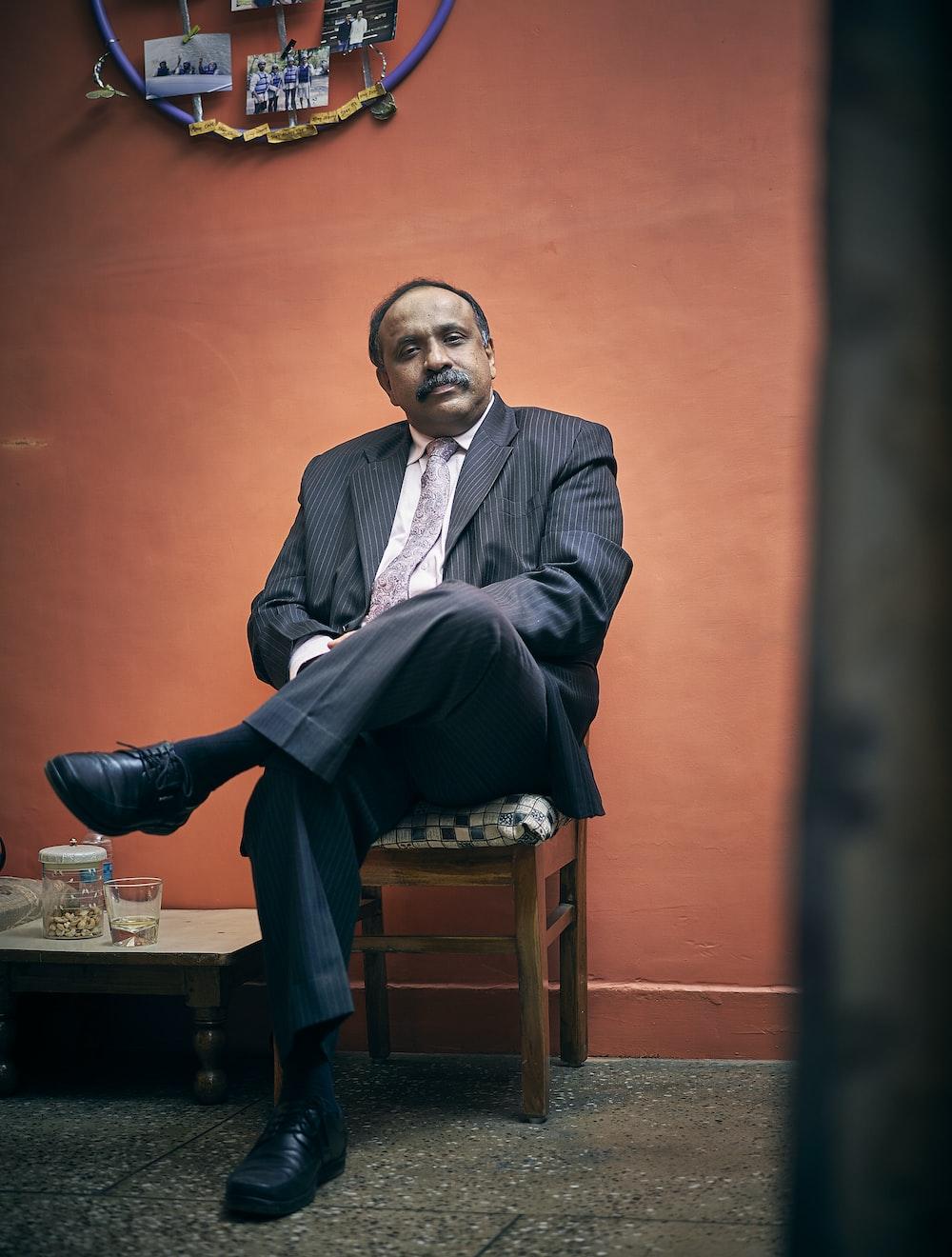 sitting man wearing black suit