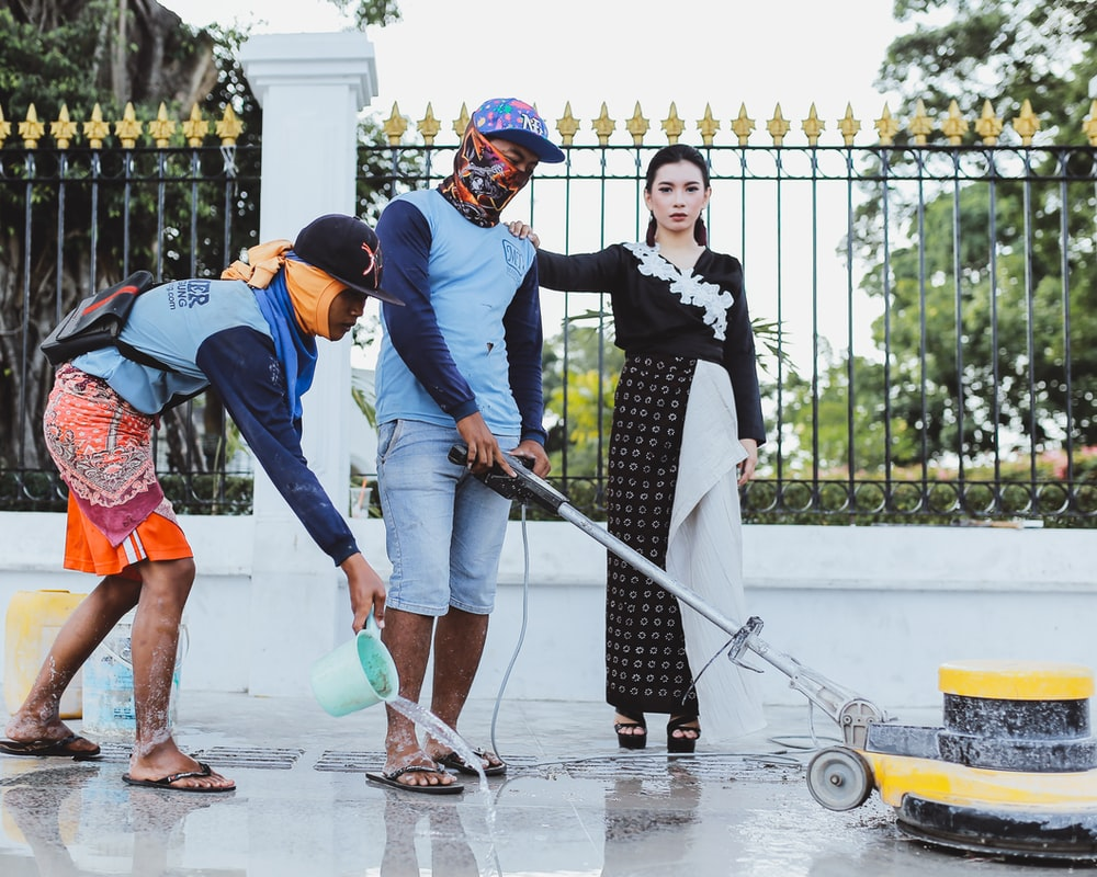 woman standing while holding on shoulder of man cleaning pathway and another man spreading water using green water dipper