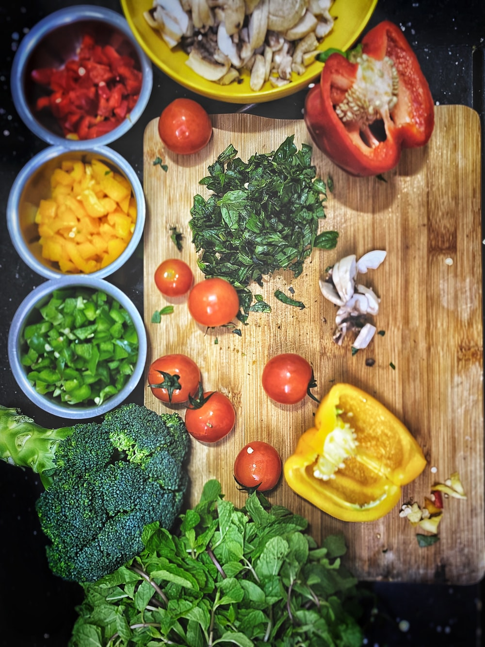 orange tomatoes near sliced yellow bell pepper, broccoli on wooden chopping board