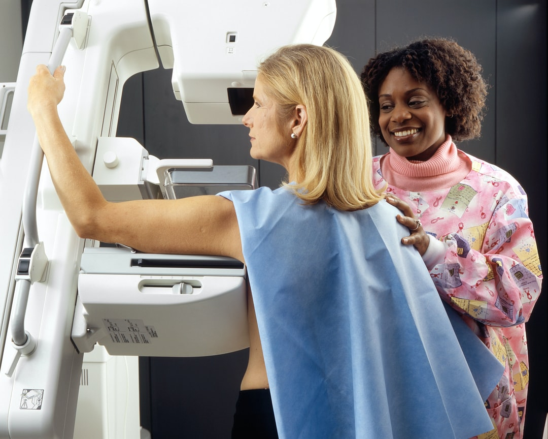 Woman Receives Mammogram. An African-American female technician positions a Caucasian woman at an imaging machine to receive a mammogram. Creator:Rhoda Baer