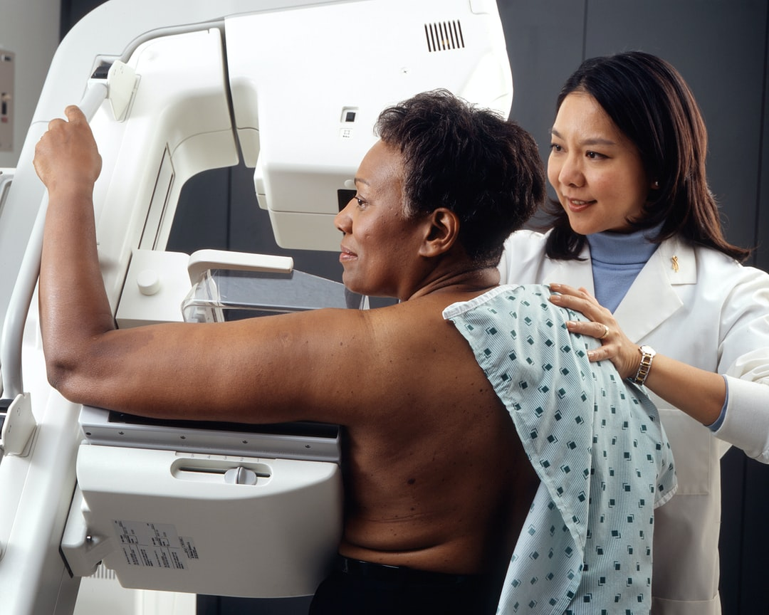 Woman Receives Mammogram. An Asian female technician positions an African-American woman at an imaging machine to receive a mammogram. Creator:Rhoda Baer