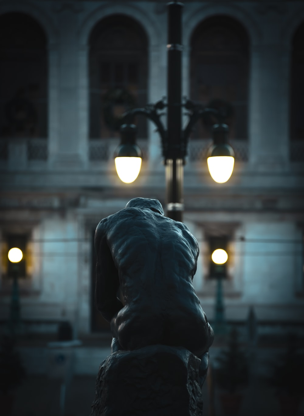 The Thinker statue near lighted street lamp during night time