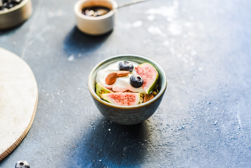 sliced fog fruit with blueberry and almonds in round green ceramic bowl