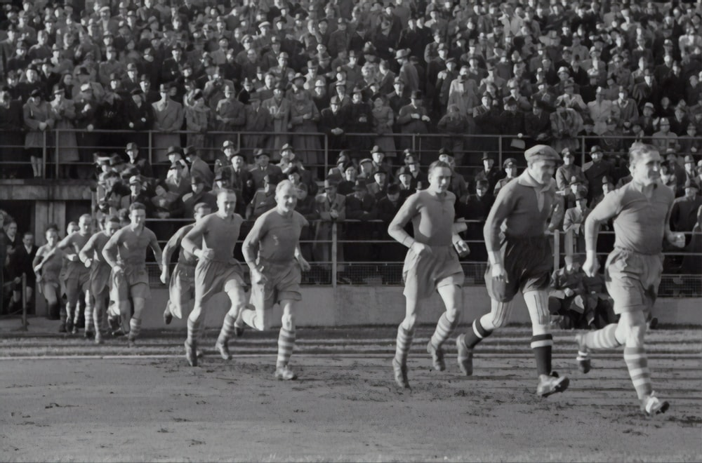 group of person running on the soccer field
