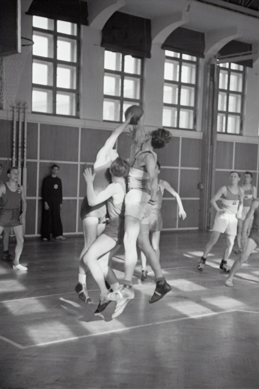 grayscale photography of men playing basketball