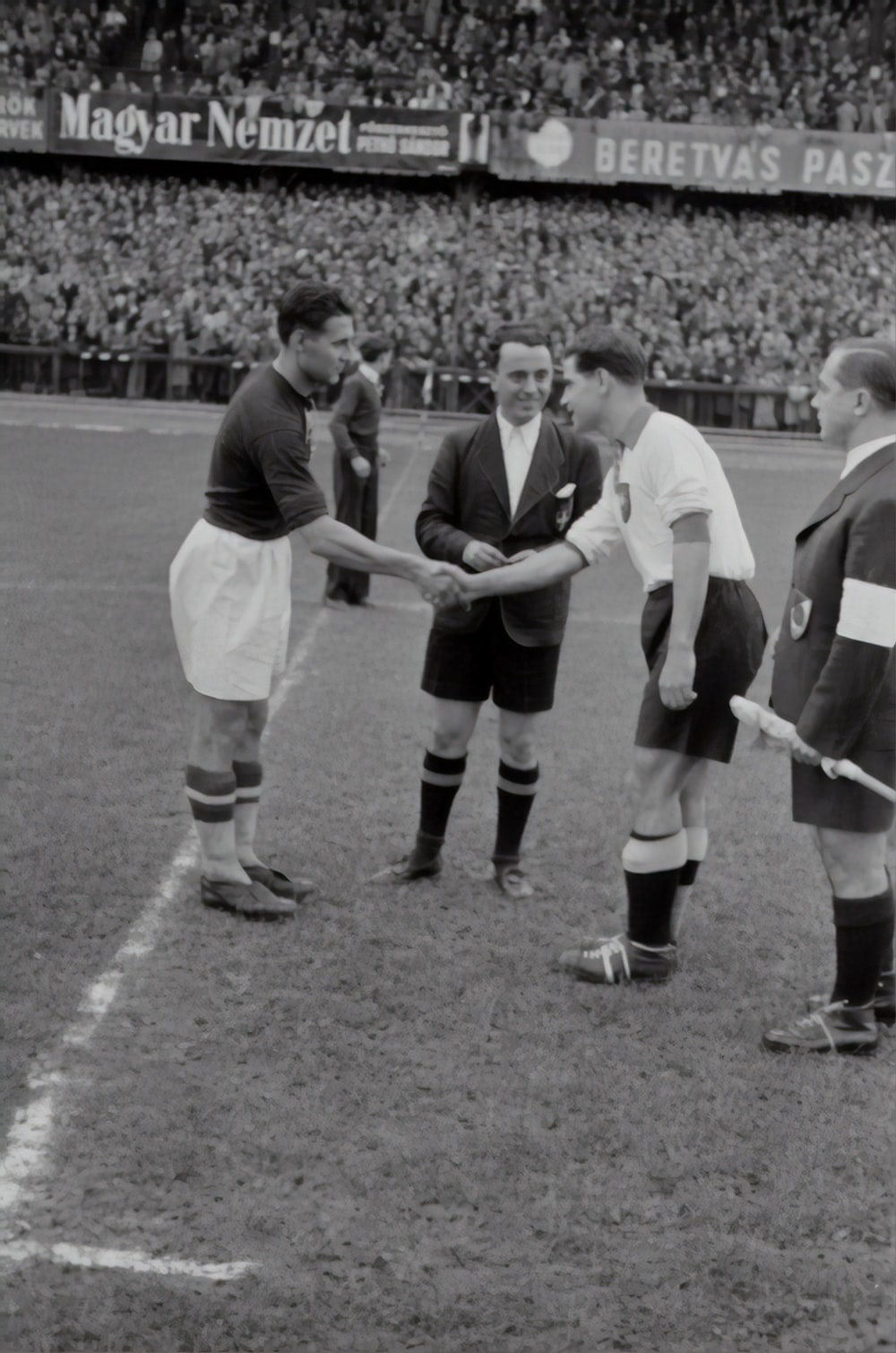 two person doing shake hands on a soccer game greyscale photograph