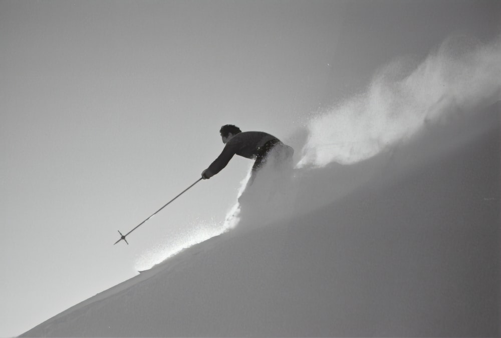 grayscale photography of man skiing on snow
