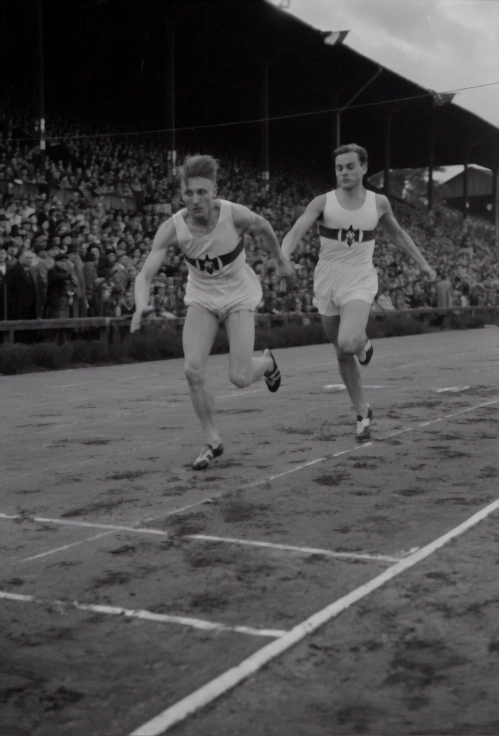 grayscale photography of men racing on track and field surrounded with people watching them