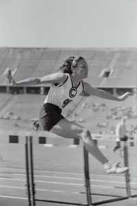 grayscale photography of woman doing hurdle