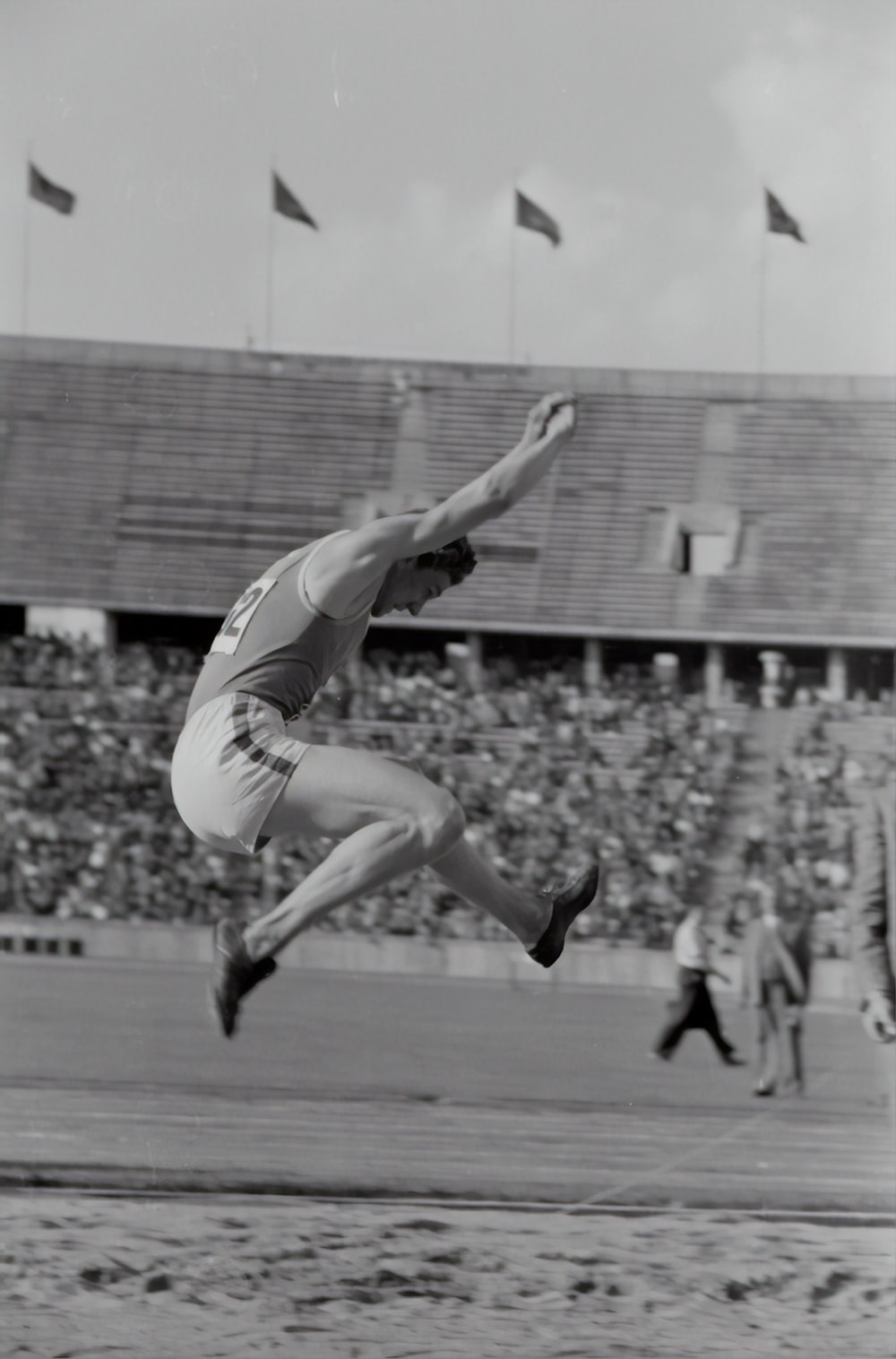 grayscale photography of man doing high jump surrounded with people watching