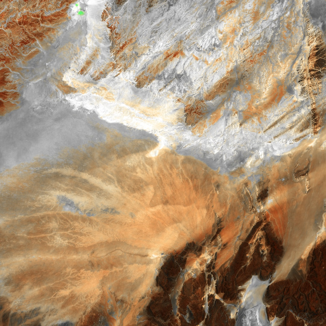 This abstract in browns and grays from central Algeria shows that some parts of Africa's Sahara Desert contain much more than dunes of wind-blown sand. Barren ridges and fragmented mountains (lower right) border a vast expanse of arid plains etched with a complex system of dry streambeds. The streambeds contain water for brief periods following rare, intense rains that often cause flash floods.