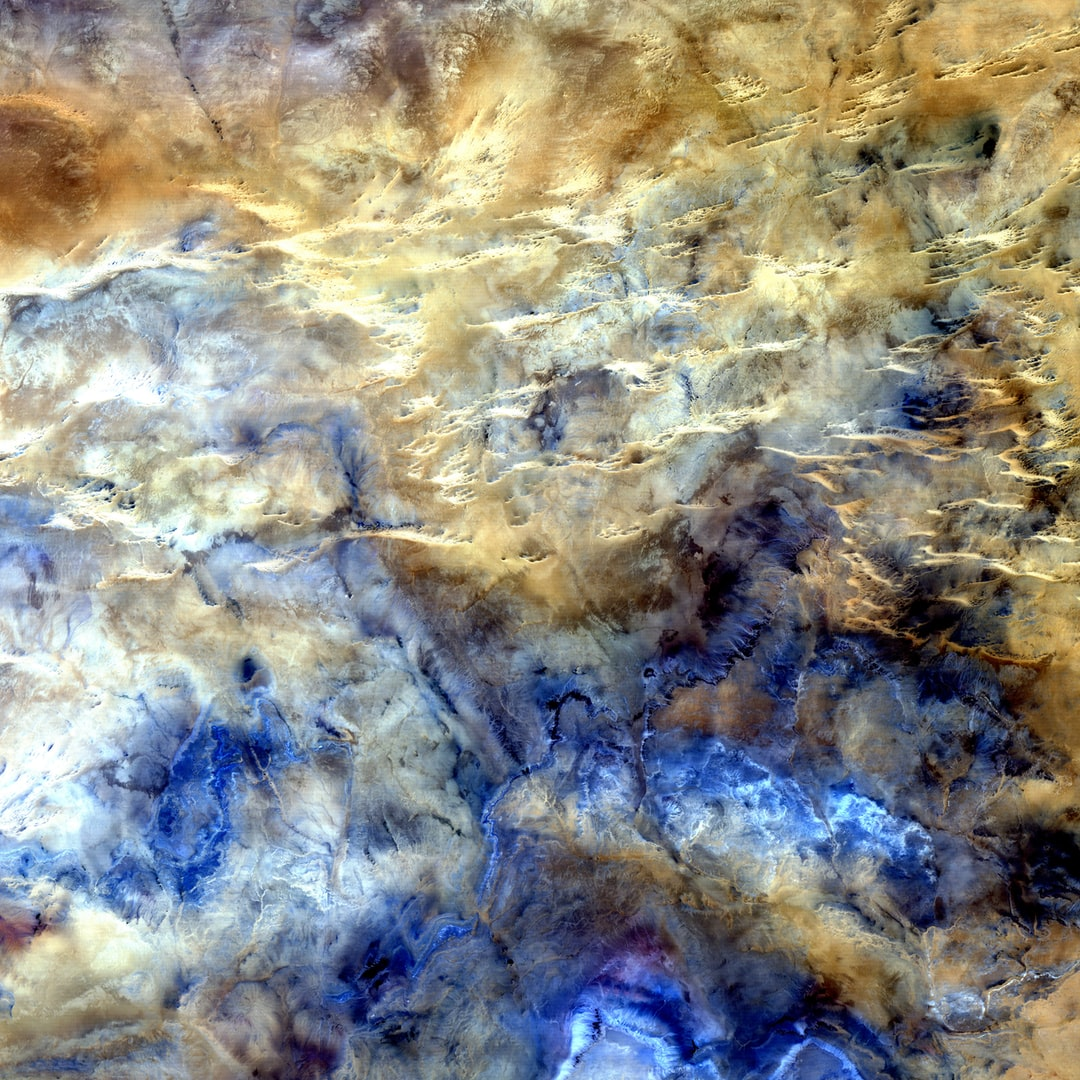 A study in shades of blue and brown is actually one of the harshest landscapes on Earth. This glimpse of Africa's Sahara Desert, located near where the borders of Mali, Niger, and Algeria converge, is truly a no man's land, a world of sand and rock without roads or settlements. The horizontal lines across the top half of the image are intrusions of igneous rock, where magma poked up to the surface from deep underground.