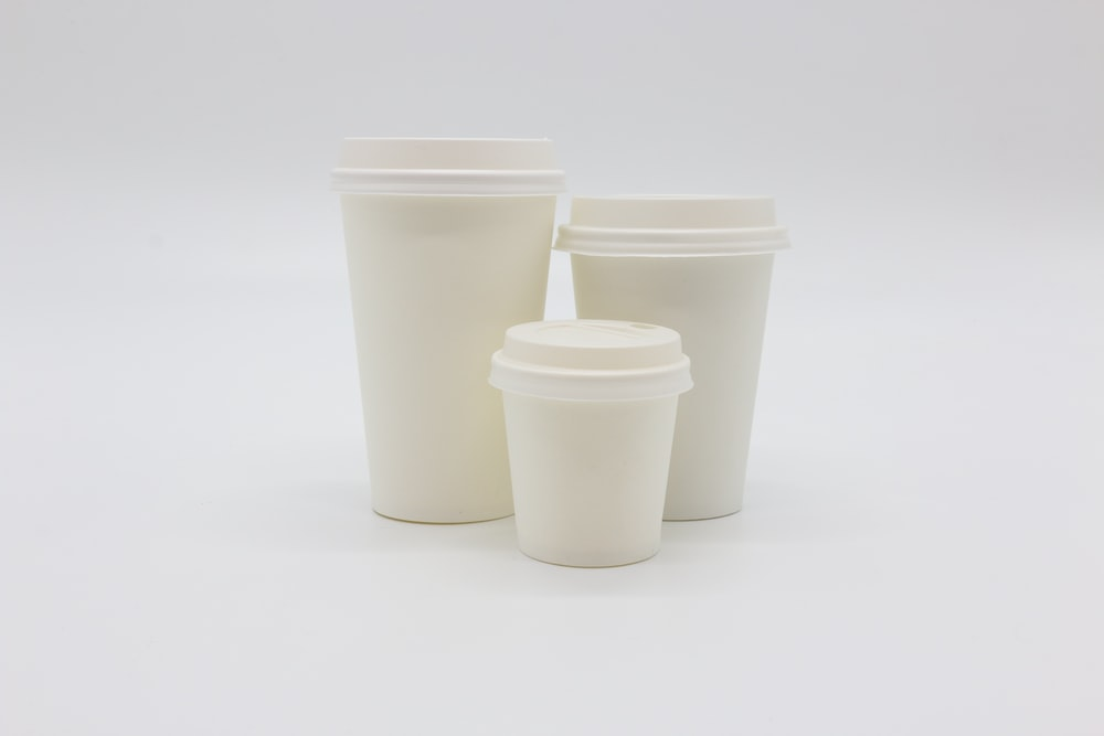 three white disposable cups