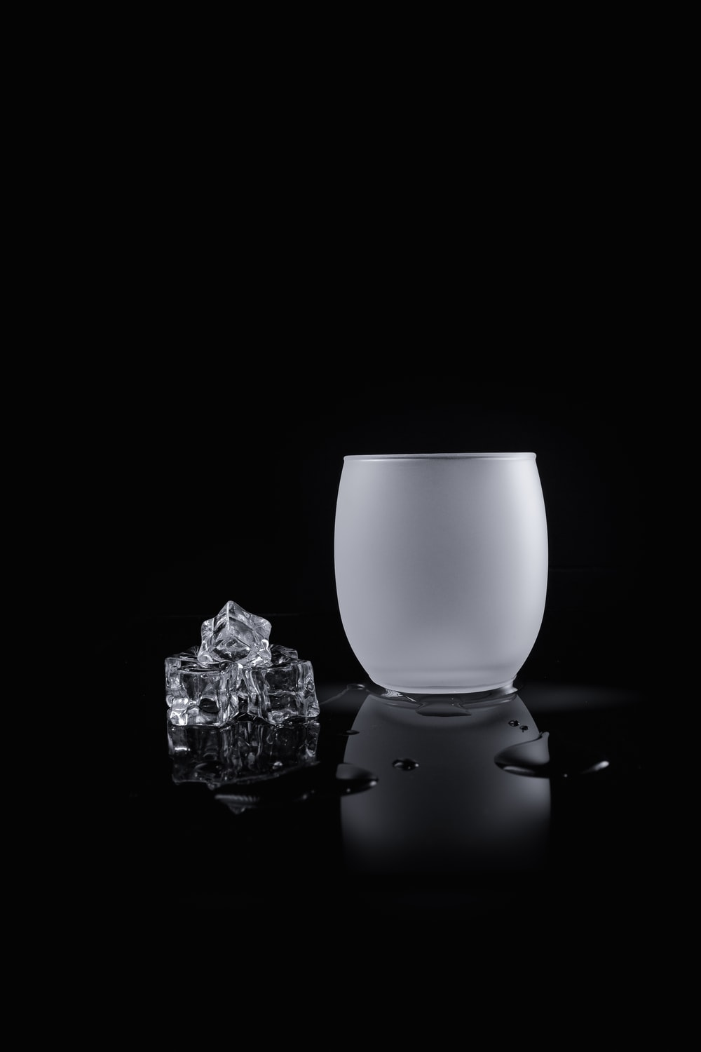 grayscale photo of ice cubes near the vase