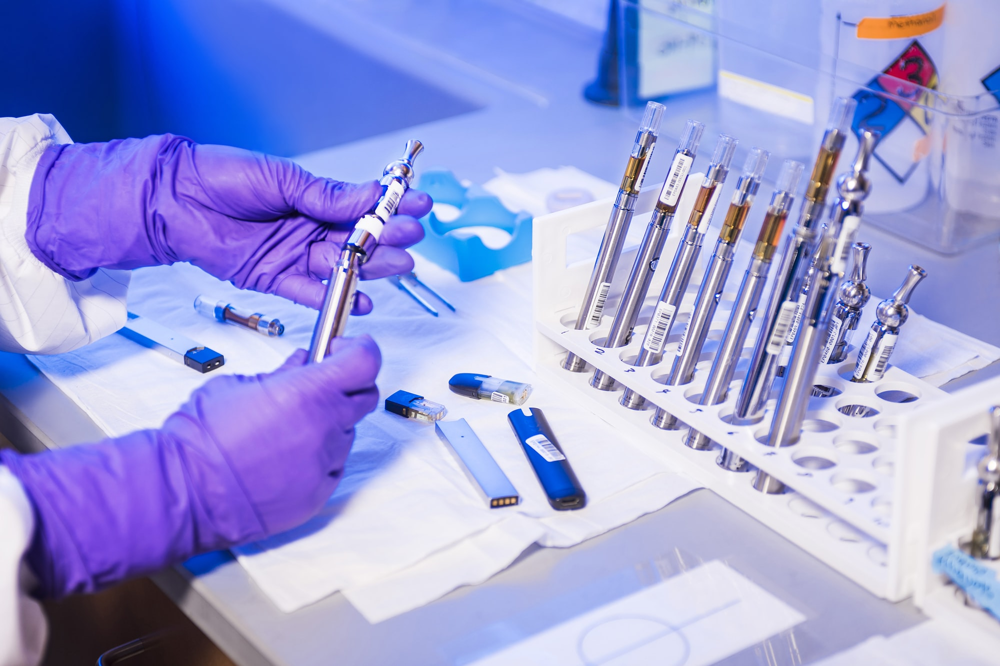 Here you see the gloved hands of a Centers for Disease Control and Prevention (CDC) laboratory technician working with electronic cigarettes, referred to as e-cigarettes, or e-cigs, and vaping pens, while inside a laboratory environment.