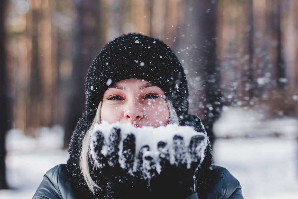 selective focus photo of woman holding snow